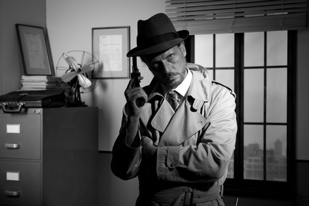 fedora hat: Attractive detective holding a revolver with the back office on the background, film noir. Stock Photo