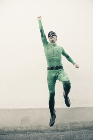 crime fighter: Green funny superhero with costume and mask flying with fist raised.