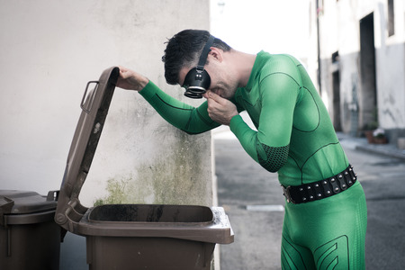 Green superhero holding his nose and opening a trash bin in the street.