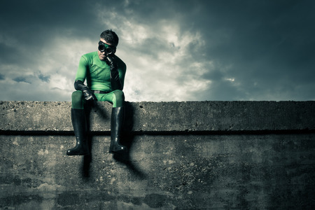 Pensive green superhero with hand on chin and cloudy dramatic sky on background.