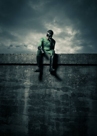 strong chin: Pensive superhero with hand on chin, sitting on a concrete wall. Stock Photo