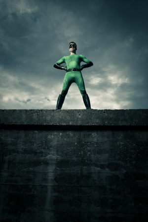 arms akimbo: Green confident superhero standing against a cloudy sky with arms akimbo. Stock Photo