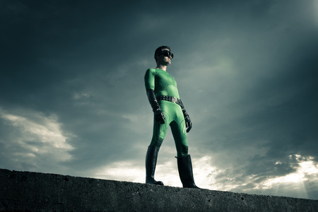Green confident superhero standing on a concrete wall with dark sky on the background.