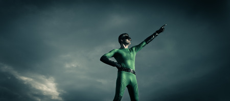 crime fighter: Green superhero pointing with dramatic cloudy sky on background.