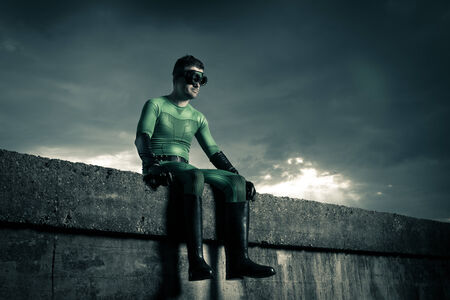 men s boot: Green pensive superhero sitting on a concrete wall with dramatic cloudy sky on background. Stock Photo