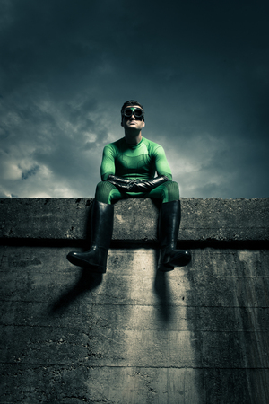 dressing up costume: Green pensive superhero sitting on a concrete wall and looking away. Stock Photo