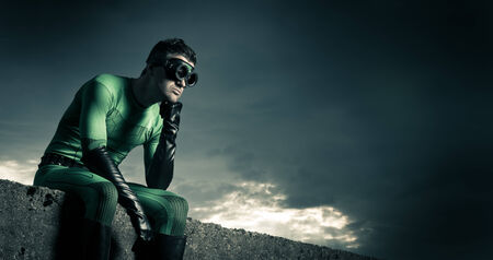 fictional character: Pensive superhero with hand on chin and dramatic cloudy sky on background. Stock Photo