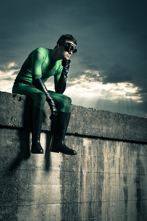 Pensive superhero with hand on chin and dramatic cloudy sky on background. Banco de Imagens