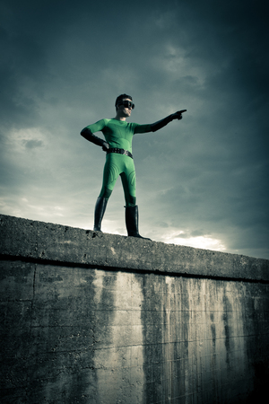 invincible: Green superhero pointing with dramatic cloudy sky on background.