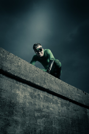hidden danger: Green superhero on all fours escaping danger on a concrete wall. Stock Photo