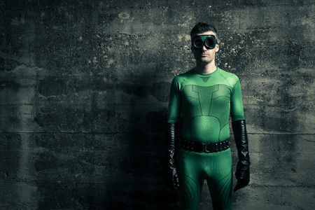 invincible: Cool green superhero standing against a concrete wall.
