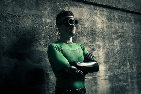 crime fighter: Confident superhero standing with arms crossed against a concrete wall.
