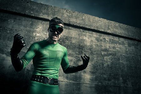 dressing up costume: Aggressive threatening green superhero against a concrete wall. Stock Photo