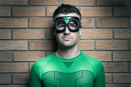 dressing up costume: Pensive green superhero looking away and leaning against a brick wall. Stock Photo