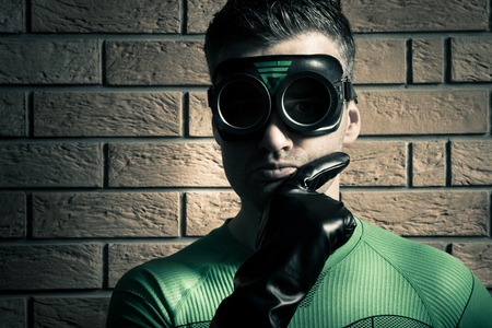 dressing up costume: Confident superhero with hand on chin and black gloves against a brick wall.