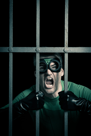 crime fighter: Angry green superhero shouting behind prison steel bars.