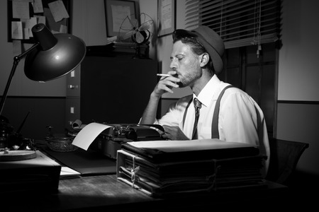 Retro reporter working late typing on a typewriter and smoking a cigarette.