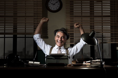 looking good: Cheerful successful reporter working at office desk with fists raised. Stock Photo