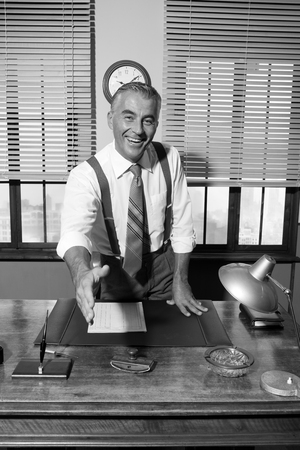 Cheerful businessman giving handshake and smiling, vintage office. photo
