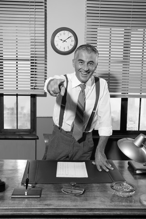 Smiling confident boss leaning to his desk and pointing finger towards camera. photo