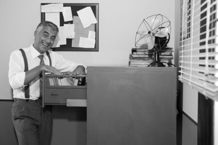 office cabinet: Cheerful smiling employee in 1950s style office searching for a file in the cabinet.