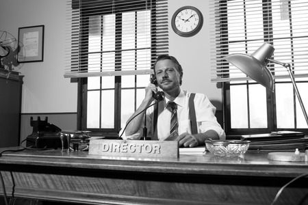 answering phone: 1950s style office: director smiling and talking on the phone.