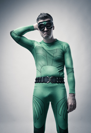 Lazy green superhero with silly expression and hand behind head.