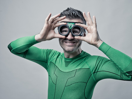 funny guys: Green smiling superhero in green costume adjusting glasses.