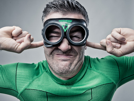 loud: Funny superhero plugging ears with fingers and waiting for a detonation.