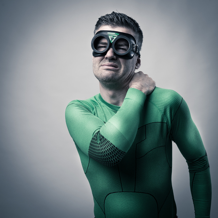 over burdened: Green superhero touching his neck and shoulder and feeling pain. Stock Photo