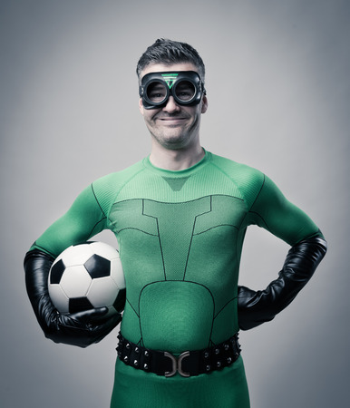 fictional character: Confident superhero in green costume holding a soccer ball.