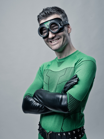 invincible: Cheerful superhero in green costume smiling with arms crossed. Stock Photo