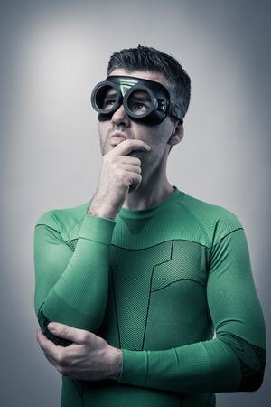 looking up: Pensive funny superhero with hand on chin looking up.