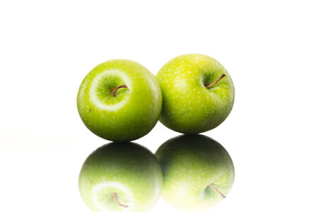 golden apple: Juicy shiny green apples on white background, healthy eating.