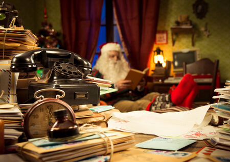 The messy desk of Santa Claus, he reading a book on background