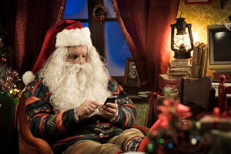 santa funny: Funny Santa Claus using his new smartphone and relaxing at home