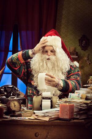 messy desk: Santa Claus contador que controla un pico largo y usando una calculadora de la vendimia en su escritorio desordenado Foto de archivo