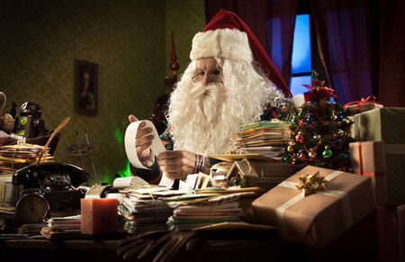 messy desk: Santa Claus accountant checking a long bill and using a vintage calculator on his messy desk