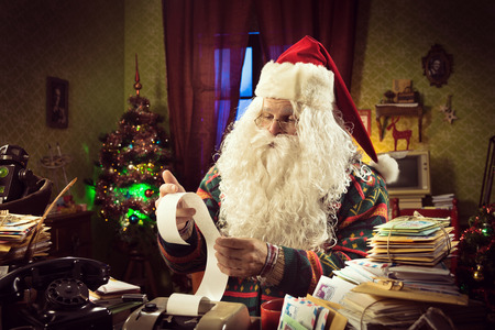 Santa Claus accountant checking a long bill and using a vintage calculator on his messy desk