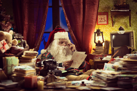 Santa Claus reading a Christmas letter sitting at his messy desk at home photo