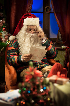 Santa Claus reading Christmas letters and relaxing on a comfortable armchair at home photo