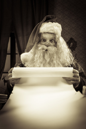 wishlist: Santa Claus reading a very long Christmas list and looking at camera