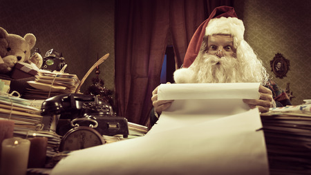 wishlist: Santa Claus reading a very long Christmas list and looking at camera.