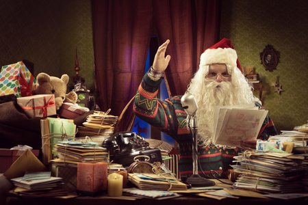Santa Claus anchorman talking on a vintage microphone and reading Christmas news photo