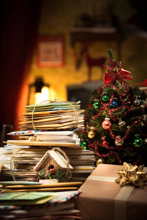 decoration messy: Messy Santa Claus home with lots of mail letters and Christmas tree on foreground