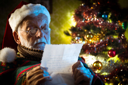 Santa Claus reading children Christmas letters at home with colorful tree on background. photo