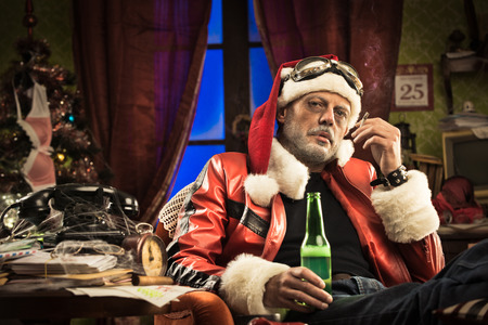 Lazy bad Santa celebrating Christmas at home alone with cigarette and beer. Stock Photo