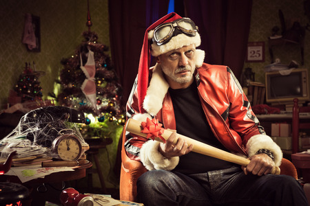 Frowning Bad Santa with baseball bat gift looking at camera
