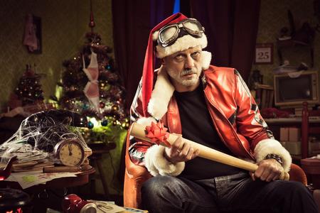 frowning: Frowning Bad Santa with baseball bat gift looking at camera