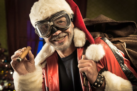 Bad Santa with goggles and cigar carrying a sack with gifts. photo